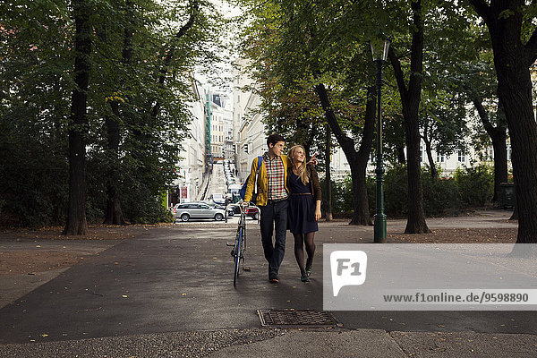 Young couple strolling in tree lined park