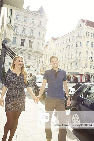 Young couple strolling along city street