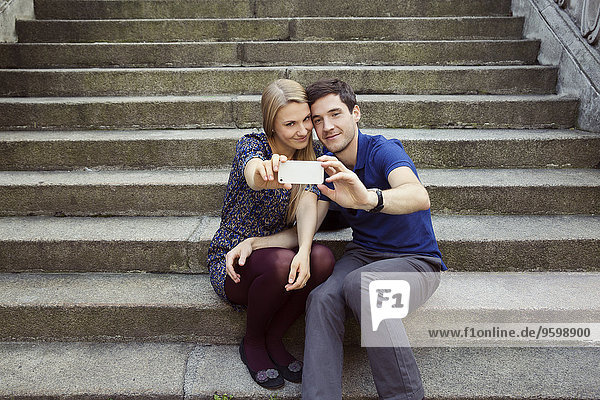 Young couple sitting on old street stairway posing for smartphone selfie