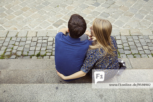 Rear view of young couple sitting on street sidewalk