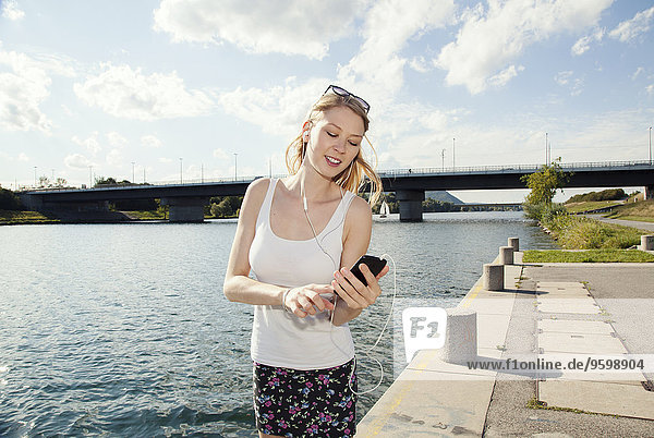 Young woman texting on smartphone on Danube Island riverside  Vienna  Austria