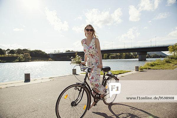 Young woman cycling along riverside  Danube Island  Vienna  Austria