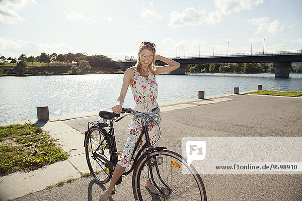 Portrait of young woman with bicycle on riverside  Danube Island  Vienna  Austria