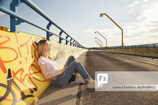 Young woman sitting leaning against graffiti wall on bridge in sunlight