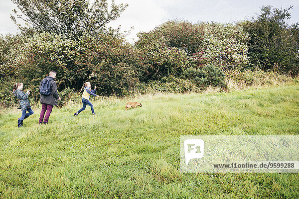 Vater und zwei Mädchen gehender Hund im Feld