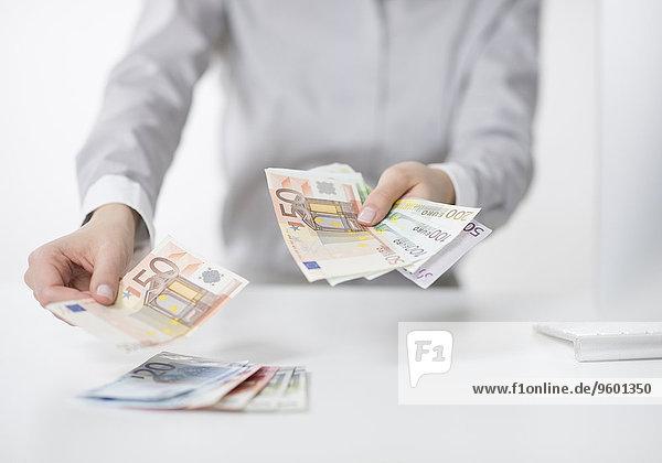 Frau blättert Euro Geldscheine auf einen Tisch