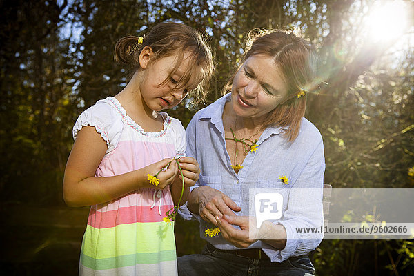 Grandmother and granddaughter looking at flower  Munich  Bavaria  Germany