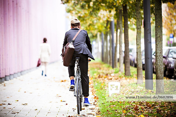 Young businessman riding bicycle  Munich  Bavaria  Germany