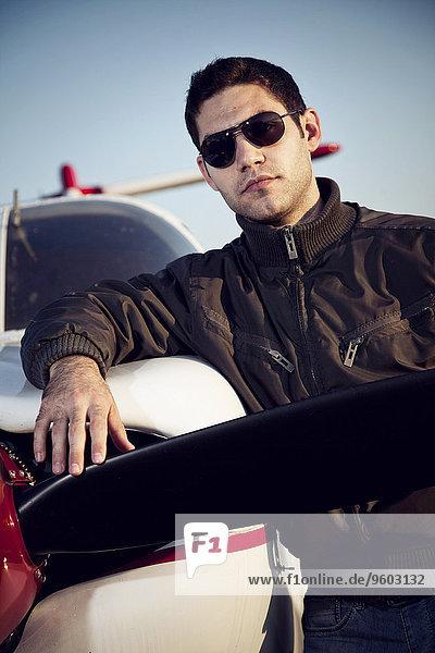 Flugzeug angelehnt Mann jung Sonnenbrille Propeller