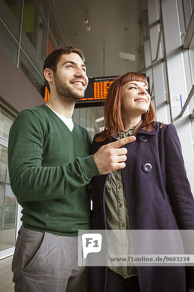 Young couple in airport building looking through window