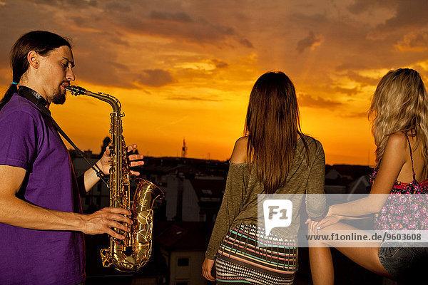 Mann Sonnenuntergang jung spielen Saxophon