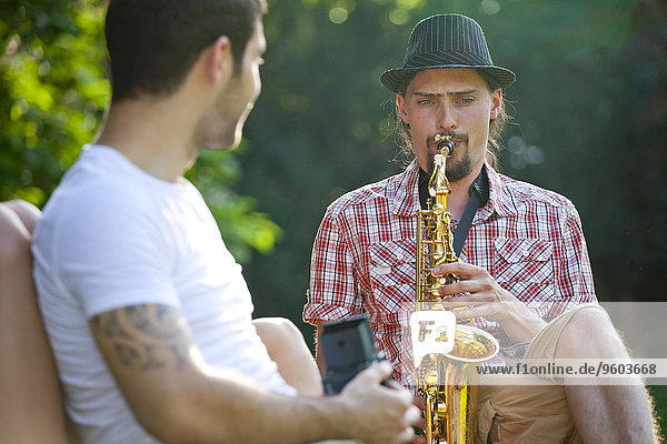 Young man playing saxophone  friend is listening