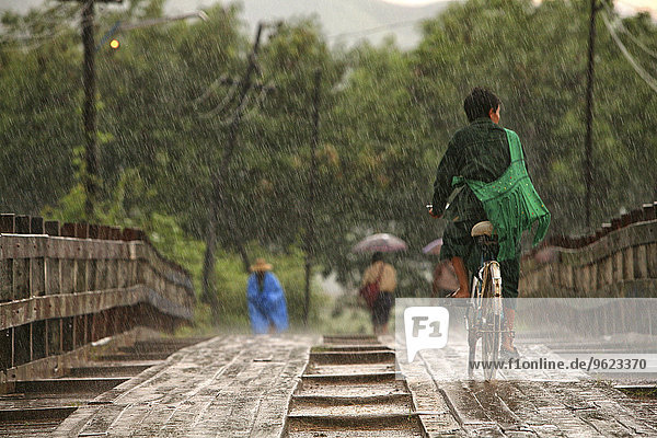 Myanmar  people on footbridge in monsoon rainfall
