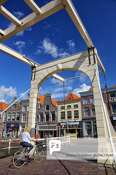 Netherlands  Alkmaar  woman on bicycle crossing bridge