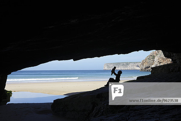 Portugal  Cape St. Vincent  Silhouette of mother and child in cave