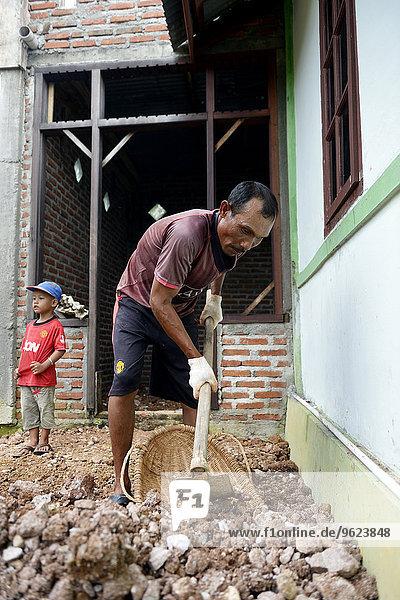 Indonesien  Aceh  Lam Teungo  Mann  der an der Erweiterung seines Hauses arbeitet.