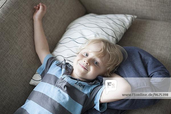 Lächelnder kleiner Junge auf der Couch liegend Lächelnder kleiner Junge auf der Couch liegend