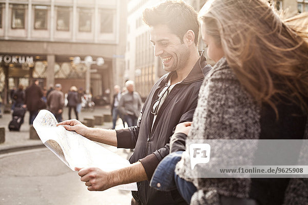 Germany  Cologne  young couple orientating with city map