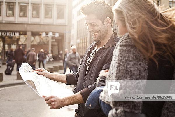 Deutschland  Köln  junges Paar orientiert sich mit Stadtplan