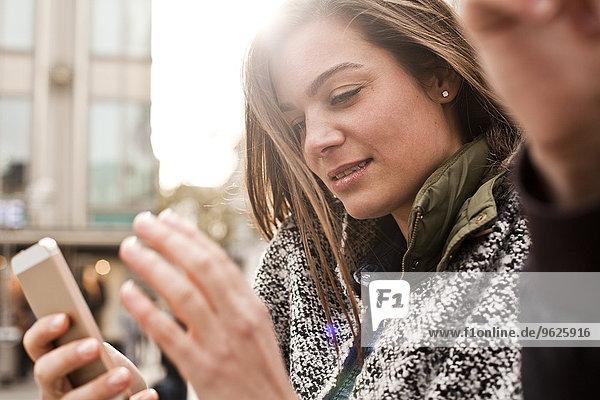 Deutschland  Köln  junge Frau mit Smartphone