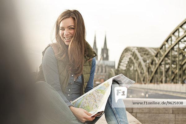 Deutschland  Köln  Portrait einer lächelnden jungen Frau mit Stadtplan am Knie Deutschland, Köln, Portrait einer lächelnden jungen Frau mit Stadtplan am Knie