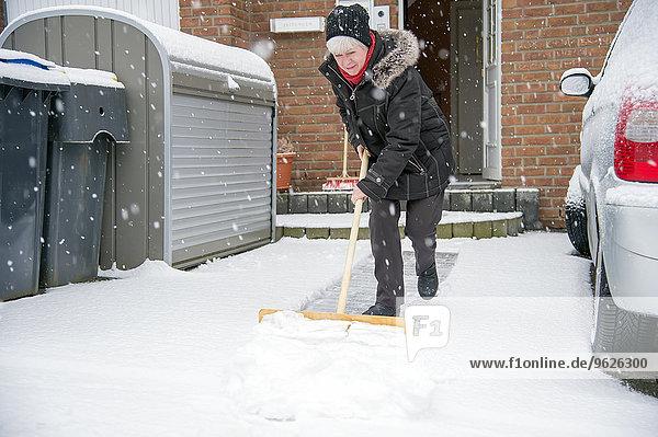 Deutschland  Grevenbroich  Frau beim Schneeschaufeln vor dem Haus