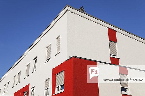 Deutschland  Köln Widdersdorf  rot-weiße Fassade eines Mehrfamilienhauses