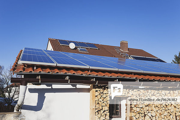 Germany  Weisenheim am Berg  solar panels on roof and storing of firewood under porch of a house