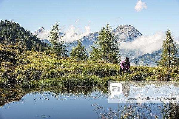 Österreich  Altenmarkt-Zauchensee  junge Frau beim Wandern in alpiner Landschaft
