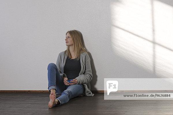 Junge Tagträumerin auf dem Boden sitzend
