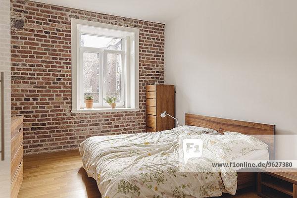 Schlafzimmer in modernem Gebäude mit Ziegelwand