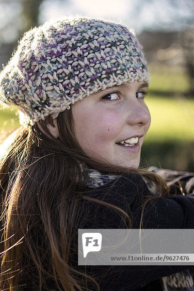 Portrait of girl wearing wool cap viewing over shoulder