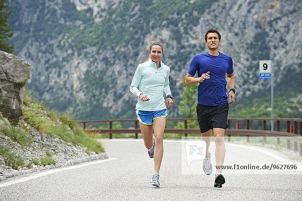 Italy  Trentino  couple running on road near Lake Garda
