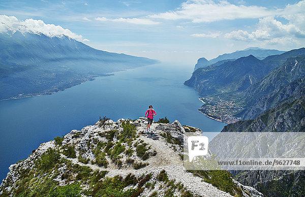 Italien  Trentino  Frau  die auf dem Berggipfel am Gardasee läuft