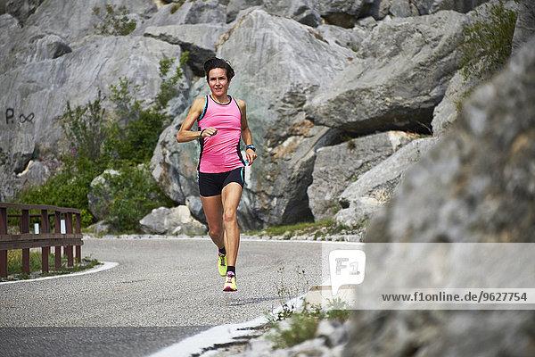 Italy  Trentino  woman jogging on road near Lake Garda