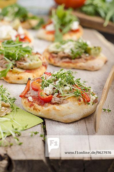 Hausgemachte Mini-Pizzas mit Rucola  Schafskäse  Artickocken  Thunfisch und Tomatensauce