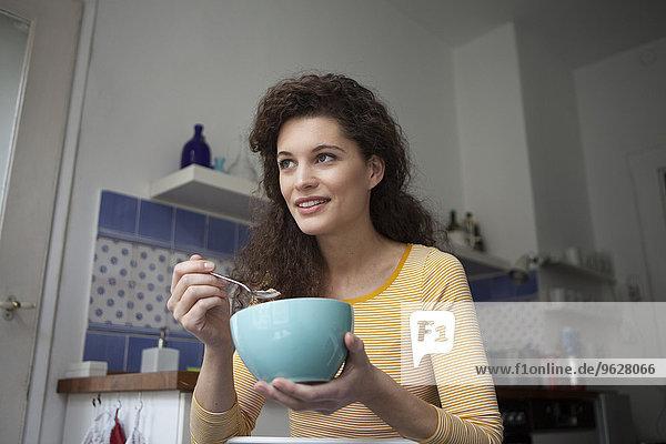Junge Frau in der Küche mit Müslischale