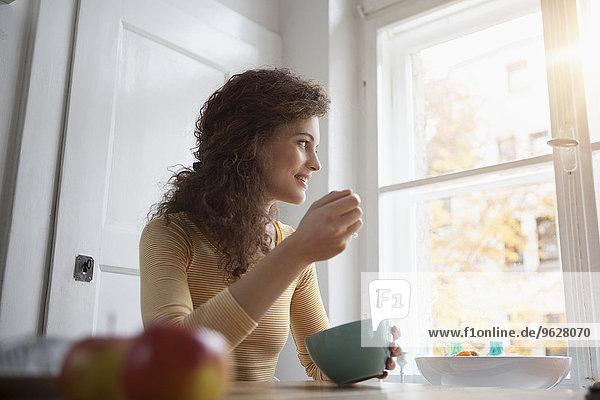 Junge Frau am Tisch beim Essen aus der Müslischale
