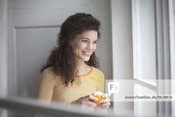 Lächelnde junge Frau schält sich orange am Fenster