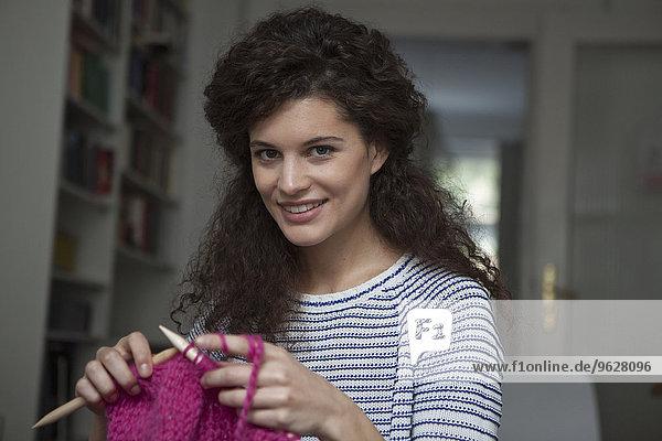 Porträt der jungen Frau zu Hause strickend