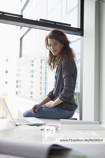 Porträt einer jungen Frau  die im Büro auf dem Schreibtisch sitzt.