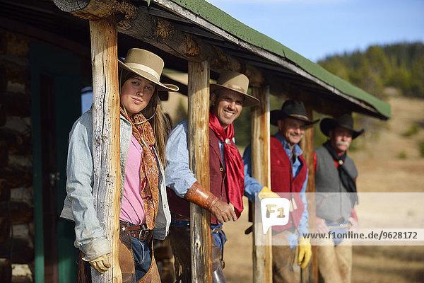 USA,  Wyoming,  Cowgirl und drei Cowboys stehen unter einer Veranda.