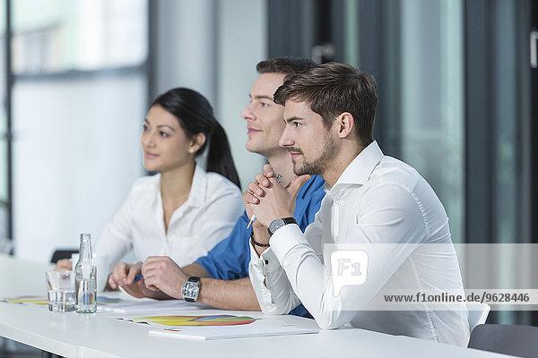 Drei Geschäftsleute  die in einem Konferenzraum zuhören