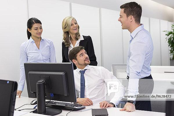 Geschäftsleute im Gespräch am Schreibtisch im Büro