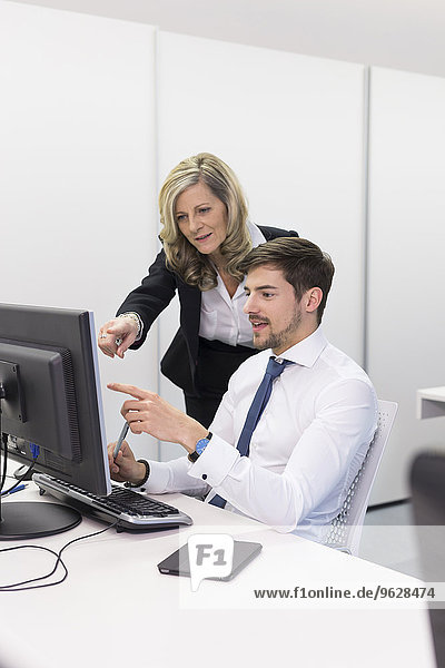 Geschäftsfrau und Geschäftsmann am Schreibtisch mit Blick auf Computerbildschirm