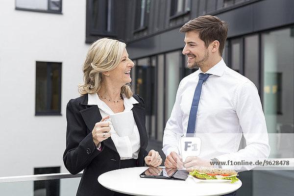 Lächelnder Geschäftsmann und Geschäftsfrau bei der Mittagspause
