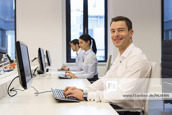 Porträt eines lächelnden Mannes am Schreibtisch mit Kollegen im Hintergrund
