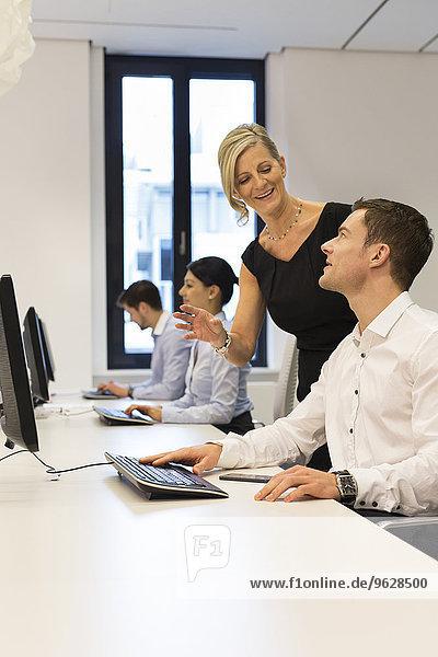 Geschäftsfrau und Geschäftsmann am Schreibtisch im Gespräch