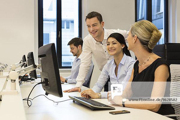 Geschäftsleute am Schreibtisch mit Blick auf den Computerbildschirm