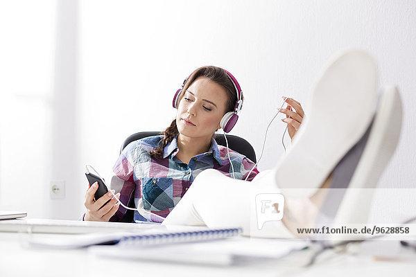 Entspannte junge Frau mit Kopfhörer am Schreibtisch